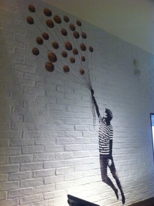 A brickwork vinyl featuring someone holding balloons